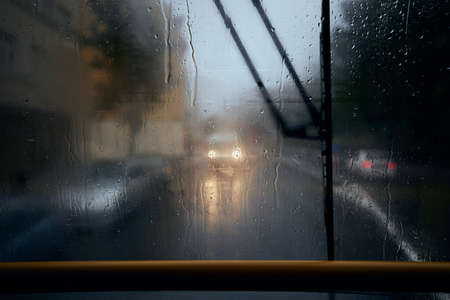 Traffic in city street during heavy rain. View from tram window. Gloomy day in Prague, Czech Republic.