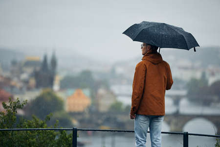 Young man with umbrella looking at city in the heavy rain. Gloomy day in Prague, Czech Republic Stock fotó