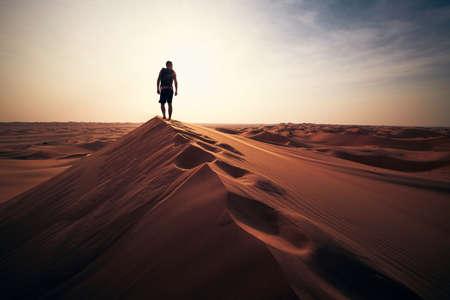 Desert adventure. Young man walking on sand dune against sunset. Abu Dhabi, United Arab Emirates Stock fotó