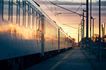 Railway at sunrise. Passenger train leaving from railroad station. Stock fotó