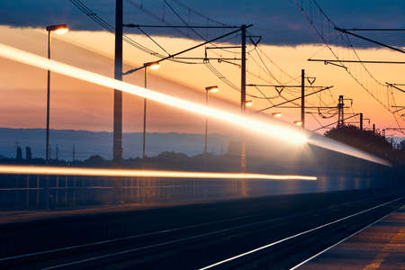 Railway at dawn. Light trails of passenger train at railroad station. Stock fotó