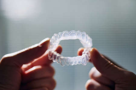 Close-up view of hand holding teeth whitening trays against window. Stock fotó