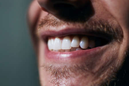 Toothy smile of young man. Close-up view of white teeth.