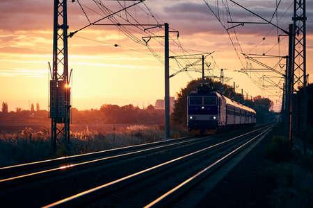 Passenger train of public transport on railroad track at beautiful sunrise. Stock fotó