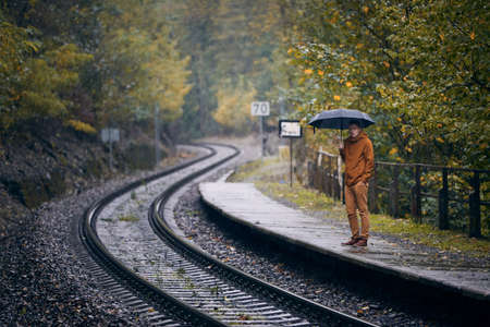 Pensive young man with umbrella waiting during rain at railroad station. Themes weather, autumn and loneliness. Stock fotó
