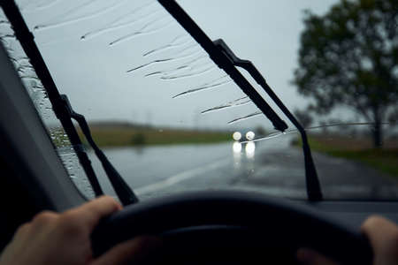 Driving in heavy rain. Raindrops on windshield of car against traffic in crossroad. Stock fotó