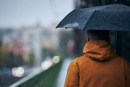 Young man with umbrella is walking on bridge during heavy rain. Gloomy day in Prague, Czech Republic Stock fotó