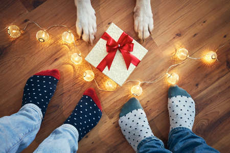 Holiday celebration at home. Family with dog around christmas gift. Stock fotó