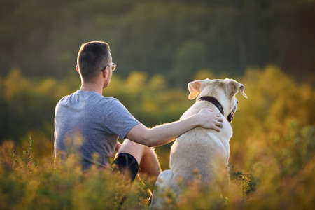 Man sitting with dog on meadow. Pet owner embracing his labrador retriever in grass.