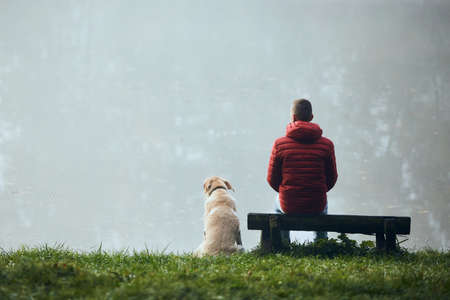 Rear view of young man with his dog on lake lakeshore. Pet owner with his labrador retriever looking at lake during foggy weather.