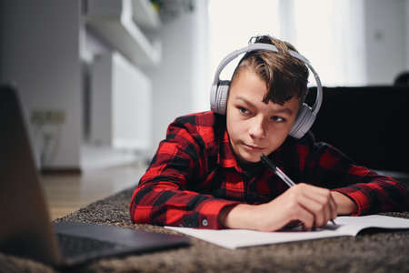 Online school lesson. Teenager learning via internet with laptop at home. Stock fotó