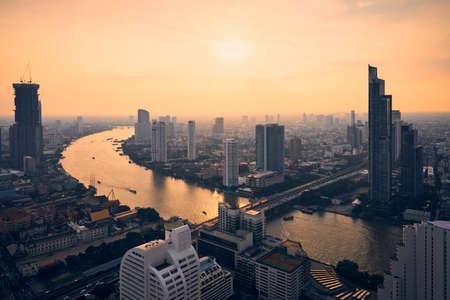 Urban skyline Bangkok during sunset. Skyscrapers near Chao Phraya river, Thailand. Stock fotó