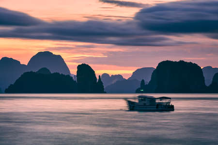 Silhouettes of Thai tropical islands at dawn. Sea between Phuket and Krabi in Thailand.