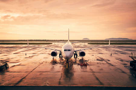 Waiting airplane at airport against sky during golden hour.