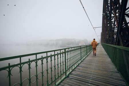 Lonely man walking on bridge against city in mysterious fog. Gloomy weather in Prague, Czech Republic.