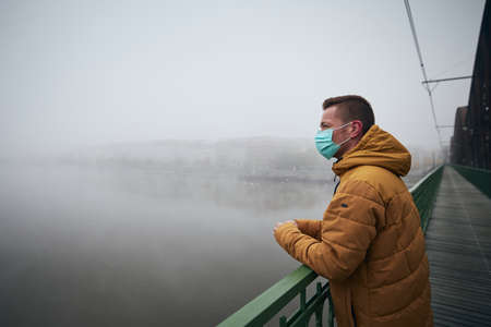 Lonely man wearing face mask on bridge against city in fog. Themes life in new normal, coronavirus and personal protection. Stock fotó