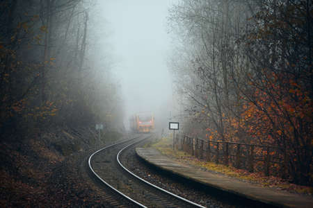 Railway during autumn weather. Passenger train leaving railroad station in foggy forest.