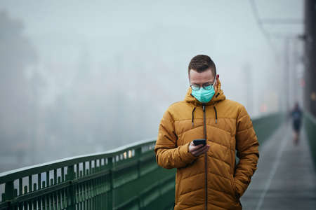 Lonely man with face mask using phone during walk on bridge against city in mysterious fog. Gloomy weather in Prague, Czech Republic.
