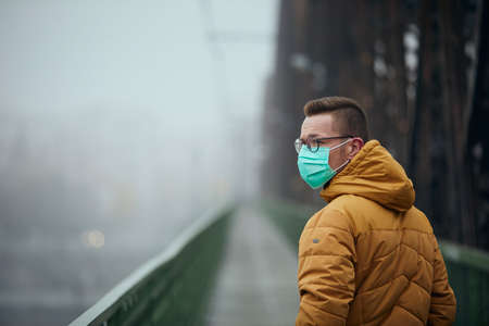 Lonely with face mask looking back during walking on bridge in fog. Themes life in new normal, coronavirus and personal protection. Stock fotó