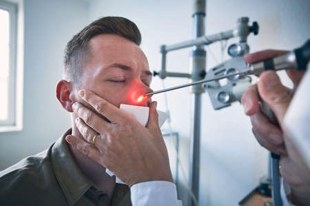 Patient at ENT clinic. Specialist doctor - Otolaryngologist doing nose examination of young man.