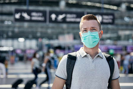 Man wearing protective face during travel by airplane. Passenger walking to check-in counter at airport terminal.