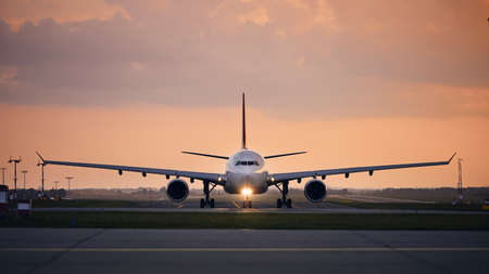 Wide-body airplane taxiing for take off. Front view of plane against airport at sunset.