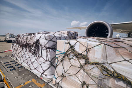 Preparation before flight. Loading of cargo containers against jet engine of freight airplane. Stock fotó