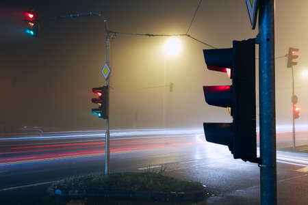 Light trail of cars passing crossroad at foggy night.