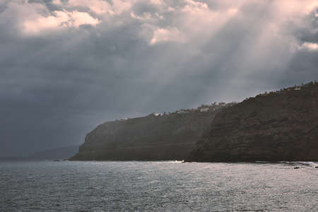 Dramatic clouds above cliffs. Coast of Teneriffe during gloomy day, Spain. Stock fotó