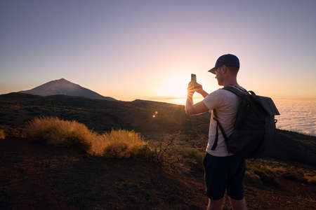 Man photograps by mobile phone against landscape at beautiful sunset. Volcano Pico de Teide in Canary Islands, Spain. Stock fotó