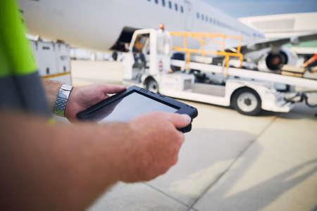 Member of ground staff preparing passenger airplane before flight. Worker using tablet against plane at airport.