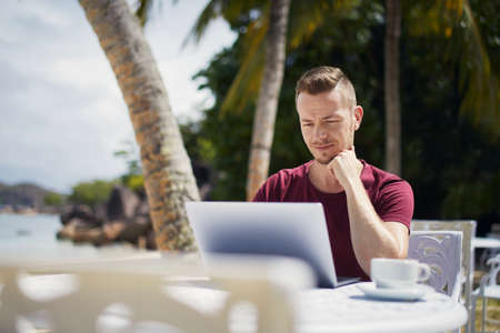 Young freelancer working on laptop from tropical destination. Man sitting under palm trees on beach.