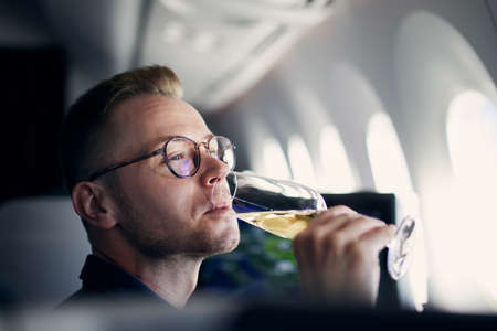 Business travel by airplane. Man looking through window and drinking champagne during flight.