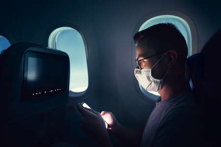 Man with face mask traveling by airplane. Passenger using phone during flight. Stock fotó
