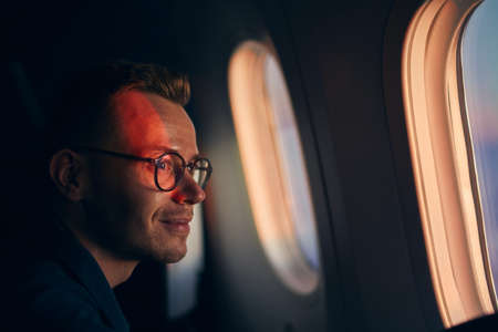 Young man with eyeglasses traveling by airplane. Passenger looking through window during flight at sunset.