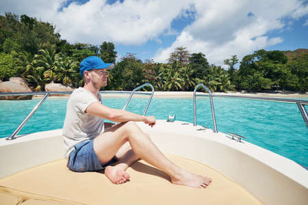 Man resting on boat against beautiful white sand beach with palm trees. Anse Lazio, Seychelles. Stock fotó