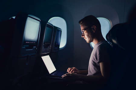 Man traveling by airplane. Young passenger using laptop during night flight.