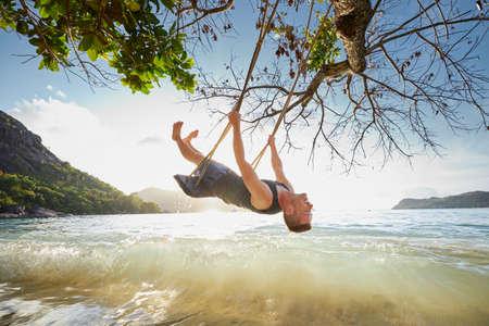 Happy man on swing enjoying holiday. Beautiful sunset on beach in Seychelles.  Stock fotó