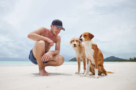 Happy man sitting with two cute dogs on white sand beach, Seychelles
