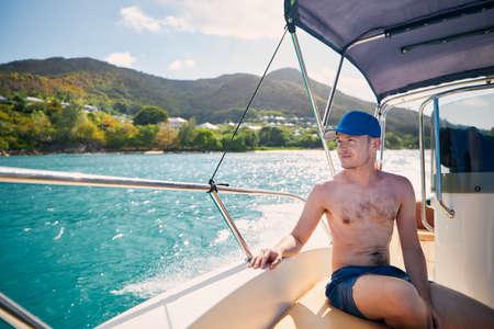 Man enjoying travel on bow of motorboat against beautiful coast of Praslin Island in Seychelles.