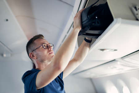 Young man travel by airplane. Passenger putting hand baggage in lockers above seats of plane.