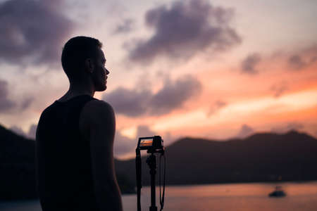 Young photographer with digital camera on tripod. Man photographing cosatline during colorful sunset.