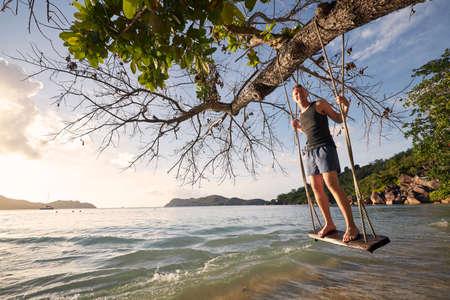 Beautiful sunny day on beach. Happy man on swing enjoying holiday in Seychelles.