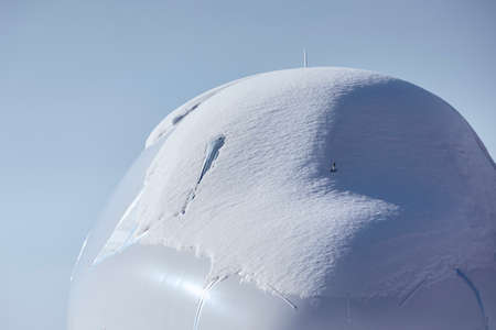 Snow covered cockpit of commercial airplane. Close-up view of plane after snowfall