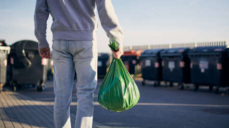 Man walking with rubbish. Rear view of person carrying plastic bag against garbage cans on street.