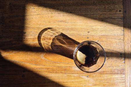 Drinking glass with cola drink. Light and shadow on wooden table.