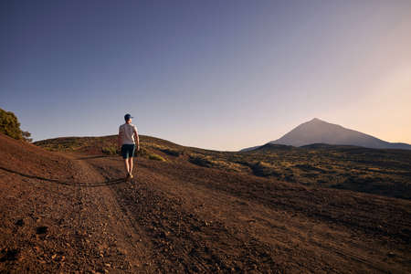 Rear view of man walking on dirt road against beautiful volcanic landscape at sunset. Volcano Teide, Tenerife, Canary Islands, Spain.
