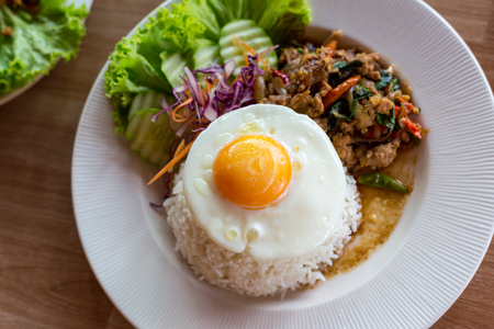 KA: Thai food, Pad Ka Phrao, fried meat with chili, garlic and holy basil. eat with rice and fried egg. Stock Photo