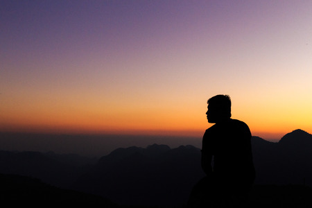 Man with arms extended toward heaven at sunrise ,success or prayer concept