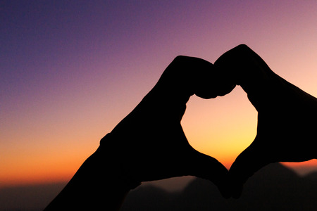 Silhouette of hands in love above the dam at the sky sunset. Stock Photo